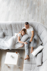 Young couple resting on sofa at home. Family relaxation lifestyle