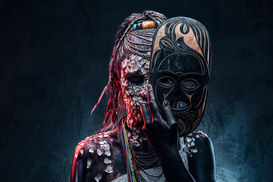 Close-up portrait of an African shaman female from the indigenous African tribe, wearing traditional costume. Make-up concept.