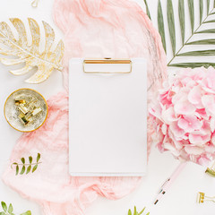 Modern home office desk workspace with blank paper clipboard, pink hydrangea flowers bouquet, tropical palm leaf, pastel blanket, monstera leaf plate and accessories on white background. Flat lay.