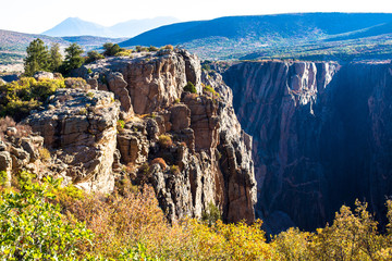 Steep, sheer cliffs and colorful fall foliage in early morning light characterize Black Canyon of the Gunnison National Park in Colorado