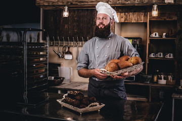 Handsome bearded chef in uniform showing tray of fresh bread in the kitchen of bakery.