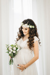 Attractive young pregnant girl in a white dress with curls, a wreath and a bouquet of flowers. Photo session waiting for the baby