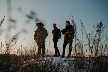 Four friends stand on a hill during a beautiful sunset. Winter trip. Relax and meeting friends. Friendship and longevity.