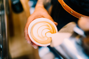 Professional barista pouring latte foam over coffee, espresso and creating a perfect cappuccino