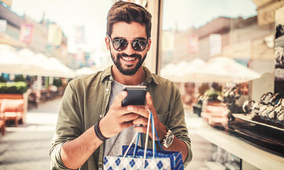 Shopping time. Modern young man with shopping bags making a phone call. Consumerism, shopping, lifestyle concept Wall mural