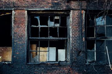 Broken window of burnt red brick building