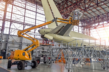 Large passenger aircraft on service in an aviation inside hangar rear view of the tail, on the auxiliary power unit.