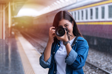 Photographer young woman taking pictures holding digital camera in station. Attractive girl travel with her camera in train station on rainy day.