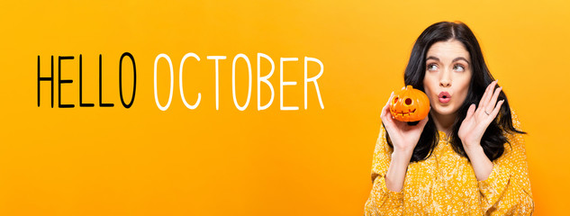 Hello October with young woman holding a pumpkin