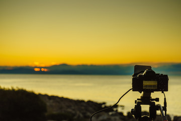 Camera taking picture film of sunrise over sea surface