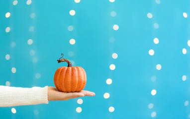Hand holding a pumpkin on a shiny light blue background