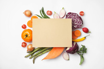 Flat lay composition with fresh vegetables and blank card for text on white background