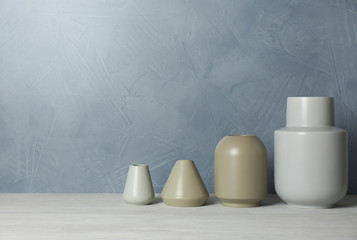 Beautiful ceramic vases on table against color wall. Space for text