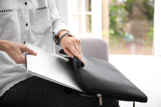 Woman putting laptop into case indoors, closeup