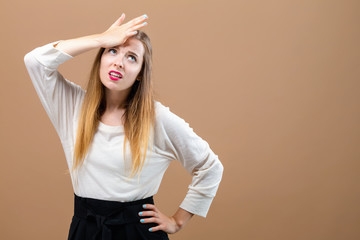 Young woman making a mistake on a brown background