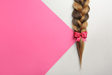 Braid and space for text on color background, top view. Healthy hair