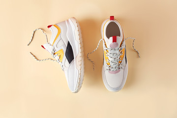 Pair of stylish sneakers on color background, top view
