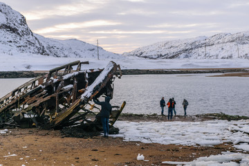 People and abandoned ship in Teriberka, Murmansk Region, Russia