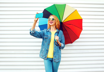 Happy day! smiling woman takes a picture self portrait on smartphone with colorful umbrella in city on white background