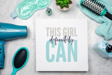 Flat lay of women's beauty products with inspirational quote