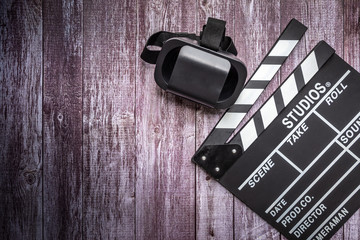 Clapperboard and VR Box / Virtual Reality glasses on wooden background.mock up, top view. Flat lay of cinema items.