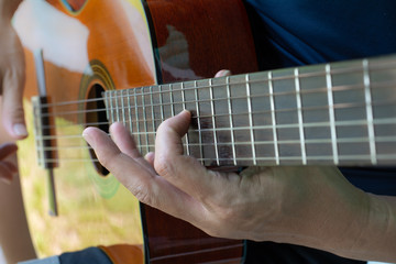 Man hand on playing guitar