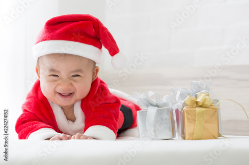 b5fb85fc5f70 Asian baby boy in Santa Claus dress on white bed for Christmas day ...