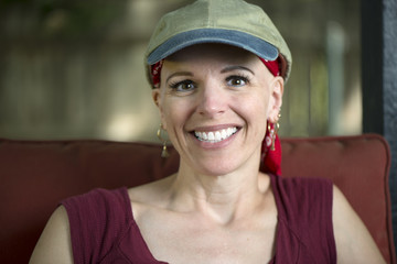 Smiling woman treatment survivor with hair loss wearing scarf and hat