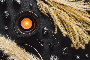 Black Cauldron with Candle and Obsidian on Black Table with Dried Feather Grass