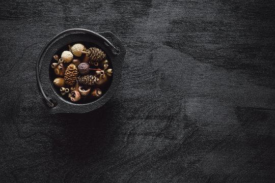 Black Cauldron Filled with Seeds on Black Table