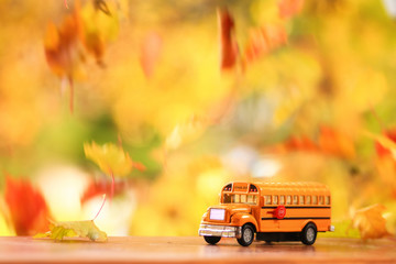 Autumn scene of an orange school bus surounded by falling leaves