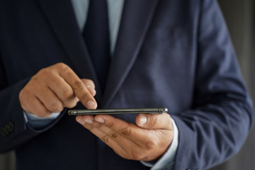 Business man hold the smartphone on the street  and copy space.