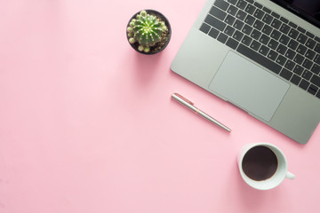 Office desk working space - Flat lay top view of modern workspace with warm coffee cup, laptop, pen and plant copy space on pastel color background. Pink color background working desk concept.