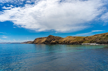 Ocean coastline with picturesque hills and deep blue water