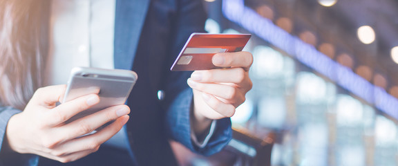 Business woman hand use credit cards and smartphones.Web banner.