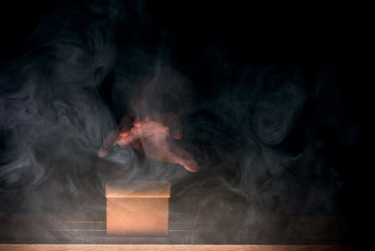 a man stretch out his hand to taking a mysterious box, smoke float up around box