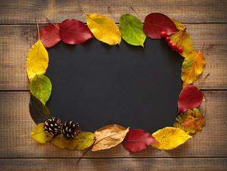 Autumn leaves forming frame on wooden surface. Thanksgiving background.