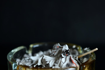 A piece of paper burning down in a glass ashtray close up