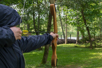 the shooter in the blue hood, pulls the bow string, to hit the target