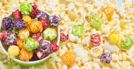 Photo sur Toile Buffet, Bar a sweet, colorful popcorn lies in a bucket and is scattered on the table