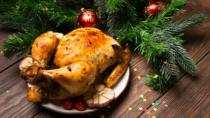 Baked chicken on a festive table on a dark background.