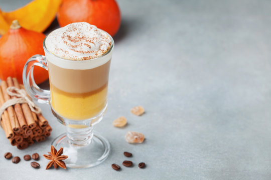 Pumpkin spiced latte or coffee in glass with space for recipe. Autumn, fall or winter hot drink.