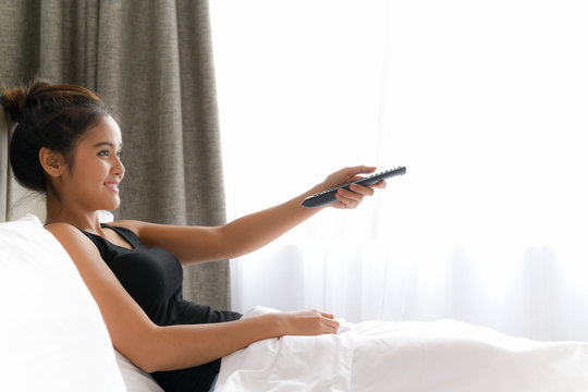 Woman In Bed Watching Television And Holding Tv Remote