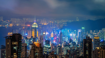 Hong Kong Downtown and Victoria Harbour. Financial district in smart city. Skyscraper and high-rise buildings. Aerial view at night.