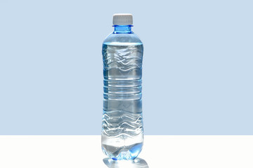 A small bottle of water on a flat surface in the rays of sunlight, isolated