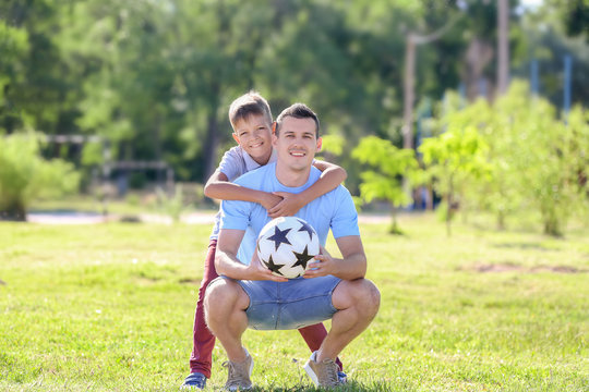 Little boy and his dad with soccer ball outdoors