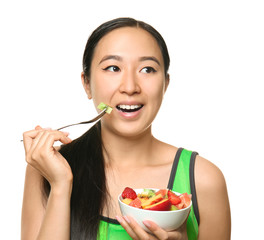Asian woman with healthy fruit salad on white background