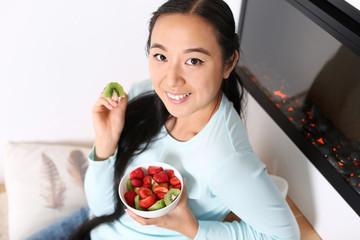 Asian woman eating healthy fruit salad at home
