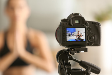 Young female blogger recording sports video at home