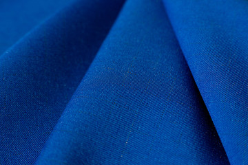 Texture of fabric and folds. A blue gabardine fabric creates a background. Fabric for sewing fashionable and stylish clothes.